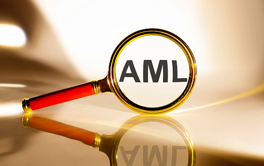 AML concept. Magnifier glass with text on the white background in sunlight.